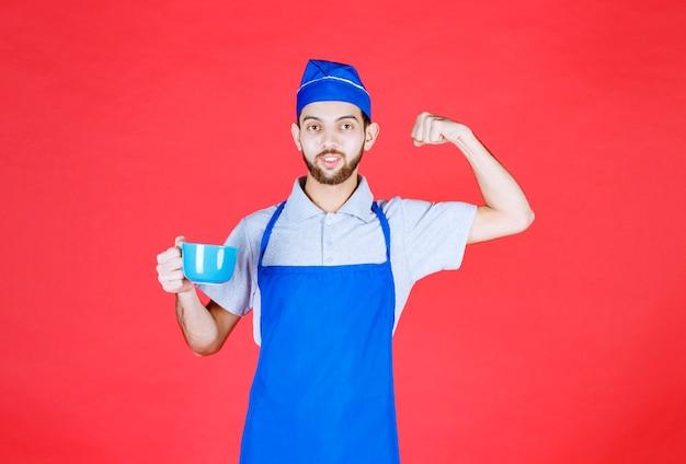 Chef-kok in blauwe schort die een blauwe keramische beker vasthoudt en zijn vuist laat zien.