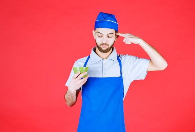Chef-kok in blauwe schort die een groene keramische beker vasthoudt en erover nadenkt.