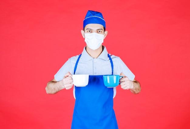 Chef-kok in blauwe schort met blauwe en witte keramische kopjes in beide handen met masker op het gezicht.