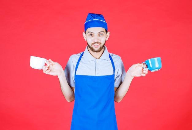 Chef-kok in blauwe schort met blauwe en witte keramische kopjes in beide handen.
