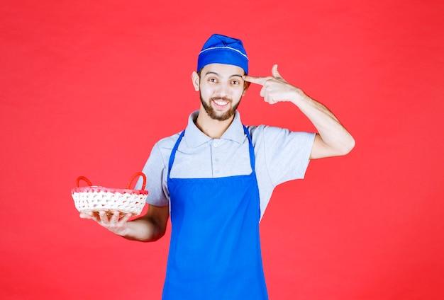 Chef-kok in blauwe schort met een broodmand bedekt met rode handdoek en denken.