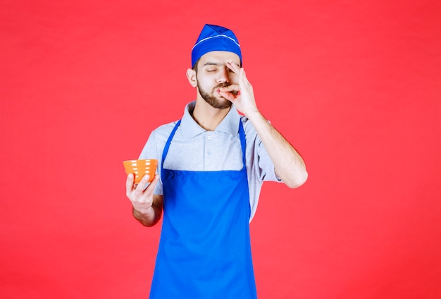 Chef-kok in blauwe schort met een gele keramische beker en een showign plezierteken.