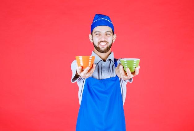 Chef-kok in blauwe schort met gele en groene keramische kopjes in beide handen.