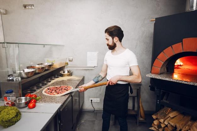 Chef-kok in de keuken bereidt pizza