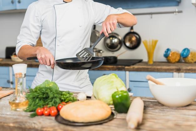 Chef-kok in de keuken koken met groenten