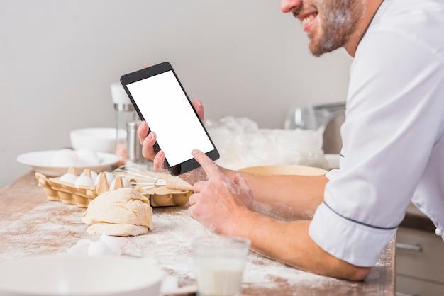 Chef-kok in de keuken met tablet schermsjabloon