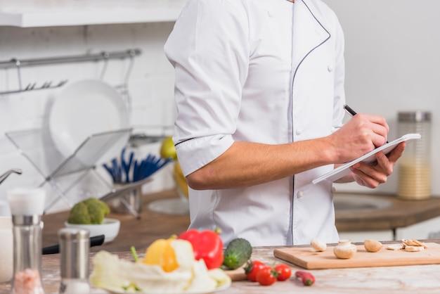 Chef-kok in de keuken schrijven van notities