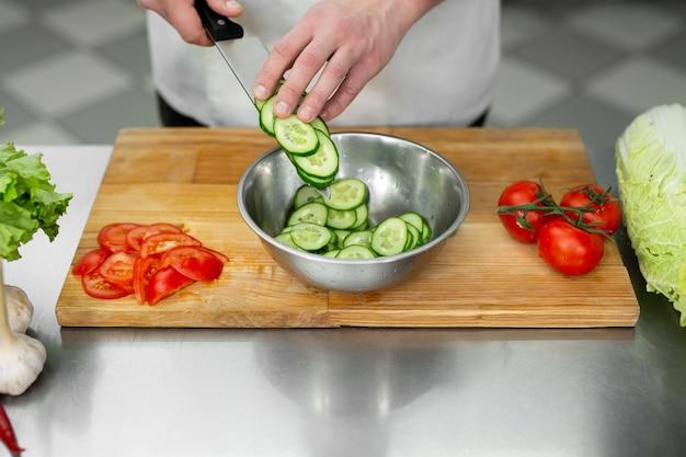 Chef-kok in de keuken snijdt verse en heerlijke groenten voor een groentesalade