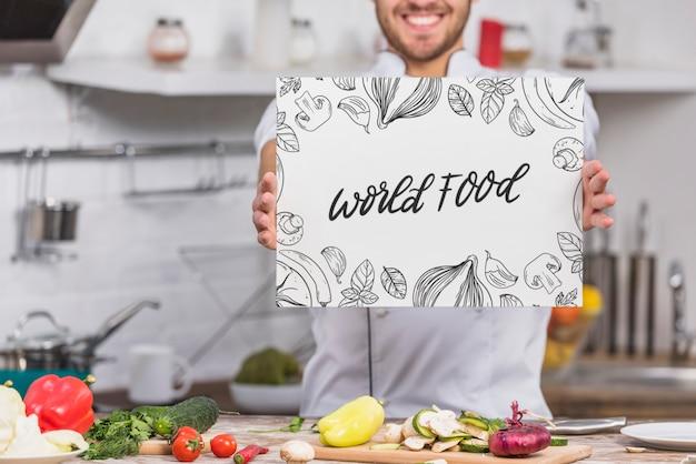 Chef-kok in de keuken toont papieren sjabloon