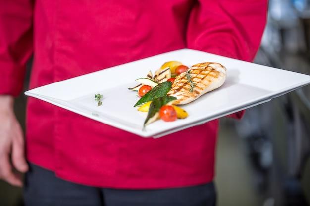 Chef-kok in de keuken van het hotel of restaurant bereidt maaltijden professionele chef-kok met een portie eten