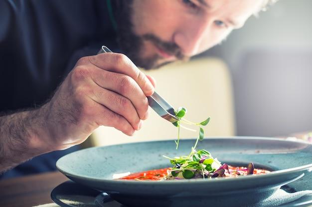 Chef-kok in de keuken van het hotel of restaurant kookt alleen handen hij werkt aan de microkruidendecoratie