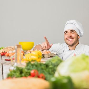 Chef-kok in de keuken wijst naar copyspace