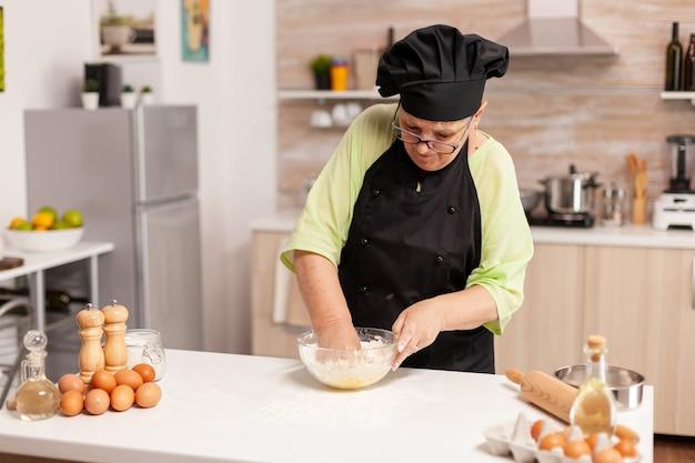 Chef-kok in de thuiskeuken die pastadeeg bereidt volgens traditioneel recept. gepensioneerde oudere chef-kok met uniform besprenkelen, zeven, zeven van grondstoffen en mengen.