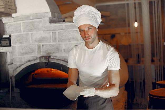 Chef-kok in een witte uniform bereiden een pizzaa