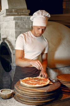 Chef-kok in een witte uniform bereiden een pizzaa