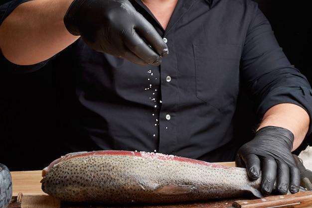 Chef-kok in een zwart shirt en zwarte latex handschoenen bereidt zalmfilet op een houten snijplank