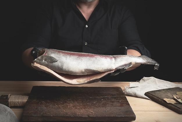 Chef-kok in een zwart shirt en zwarte latex handschoenen houdt een rauw karkas zonder zalm boven een bruine houten snijplank