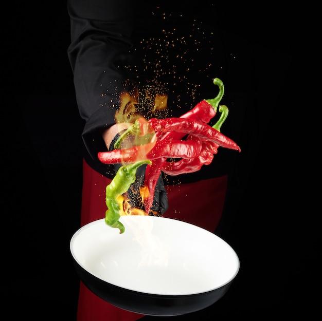 Chef-kok in een zwart uniform houdt een ronde pan en gooit rode en groene hele chilipepers in een brandend vuur