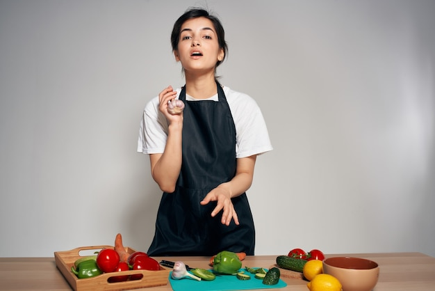 Chef-kok in een zwarte schort in de keukengroenten die thuis koken