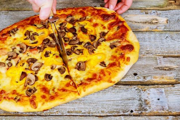 Chef-kok in handschoenen die hete klaar pizza snijden door pizzasnijder, close-up te rollen