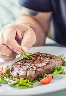 Chef-kok in hotel- of restaurantkeuken die alleen handen kookt bereide biefstuk met groente