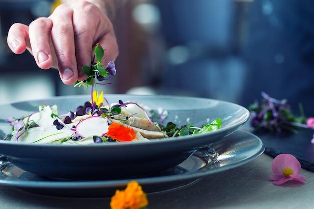 Chef-kok in hotel- of restaurantkeuken koken, alleen handen. hij werkt aan de microkruidendecoratie. groentesalade bereiden met stukjes gegrild kippenvlees - maagdelijke entrecote