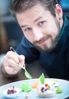 Chef-kok in hotel- of restaurantkeuken koken, alleen handen. hij werkt aan de microkruidendecoratie. voorgerecht bereiden - ganzenpastei met groente