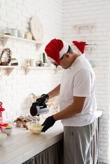 Chef-kok in kerstmuts koken een dessert in de keuken slagroom