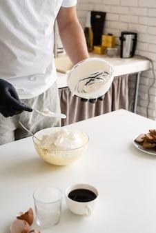 Chef-kok in kerstmuts koken een dessert in de keuken
