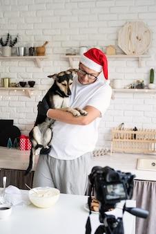 Chef-kok in kerstmuts met zijn hond in de armen koken in de keuken en video maken