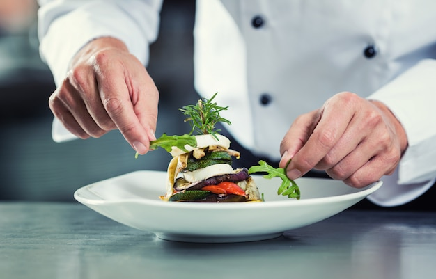 Chef-kok in restaurant die plantaardige schotel versieren