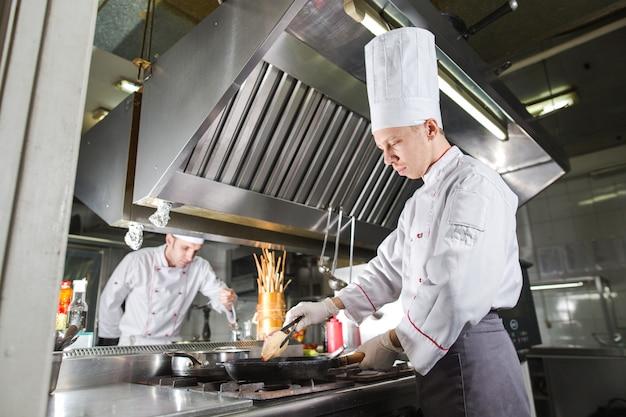 Chef-kok in restaurantkeuken bij fornuis met pan, het koken