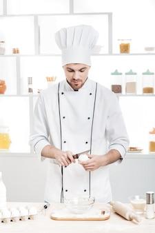 Chef-kok in uniform breekt eieren in een kom om deeg in de keuken te bereiden