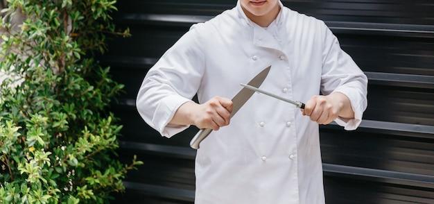 Chef-kok in uniform een groot mes van het keukenmes slijpen met een stalen slijpstok.