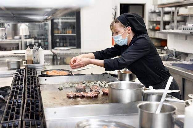 Chef-kok in uniform koken in een commerciële keuken