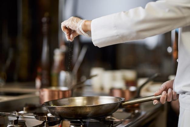 Chef-kok in wit uniform zout zijn kookkunsten in de pan