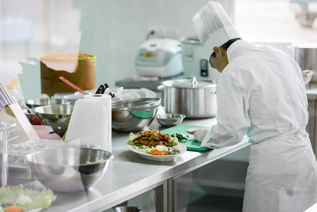 Chef-kok in witte chef-kok uniform gaan koken in de keuken om eten te serveren aan klanten in het restaurant van het hotel