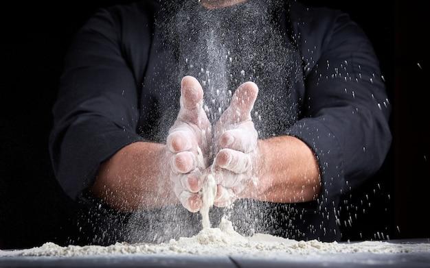 Chef-kok in zwart uniform giet witte tarwemeel uit zijn handen