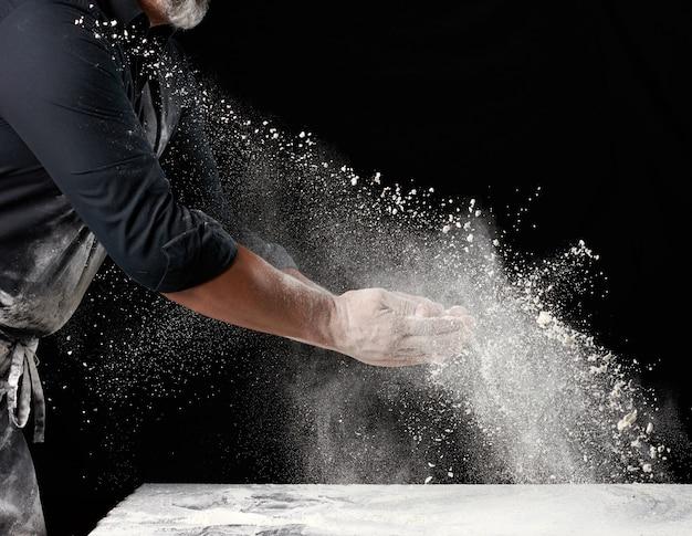 Chef-kok in zwart uniform strooit wit tarwebloem in verschillende richtingen, product verspreidt stof, zwarte achtergrond, deeltjes verspreiden zich en bevriezen in de lucht