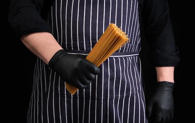 Chef-kok in zwarte latex handschoenen, gestreepte schort houdt rauwe lange gele spaghetti gemaakt van durumtarwe