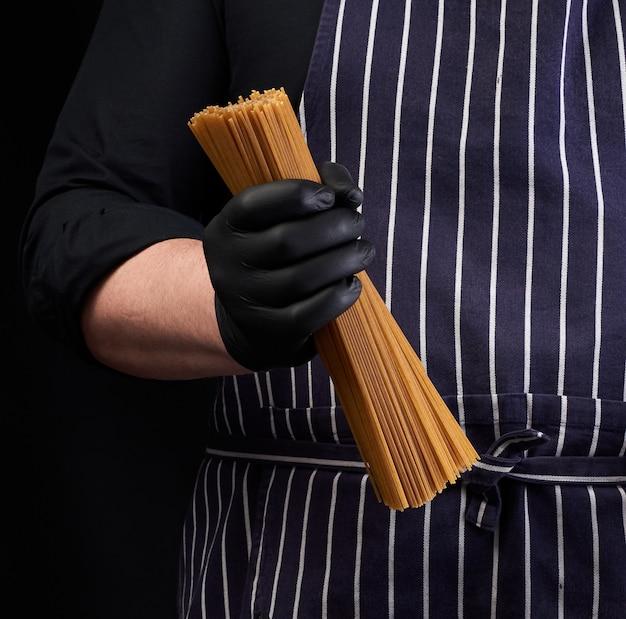 Chef-kok in zwarte latex handschoenen, gestreepte schort houdt rauwe lange gele spaghetti