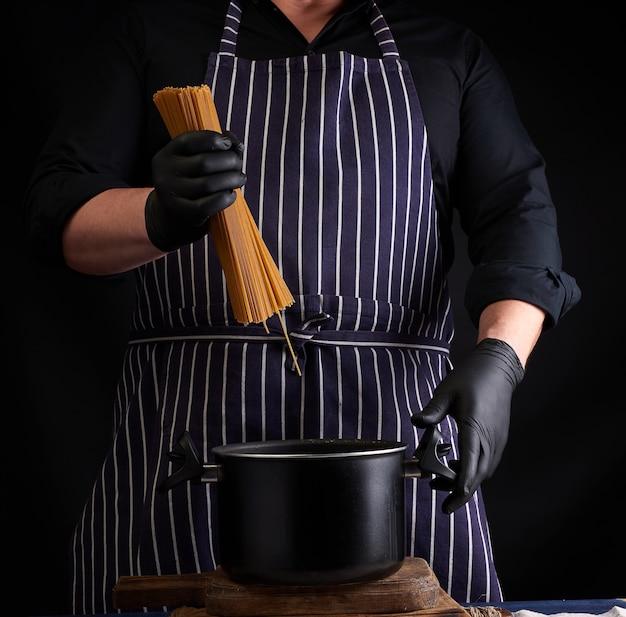 Chef-kok in zwarte latex handschoenen, gestreepte schort houdt rauwe lange spaghetti over de pan
