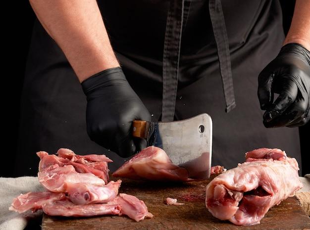 Chef-kok in zwarte latex handschoenen houdt een groot mes en snijdt in stukken rauw konijnenvlees