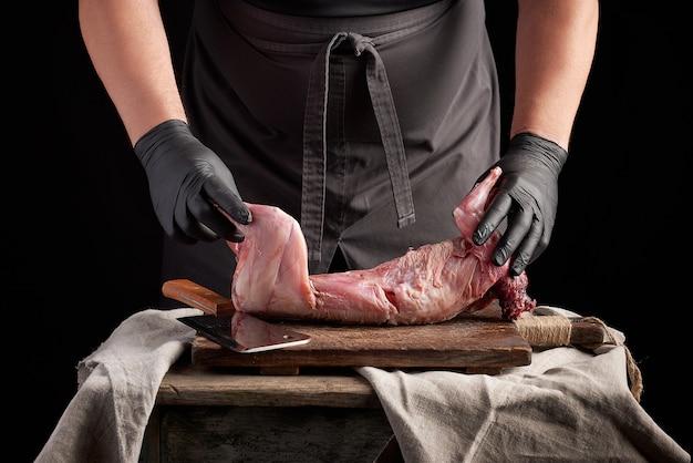 Chef-kok in zwarte latexhandschoenen houdt een heel konijnenkarkas op een bruine snijplank
