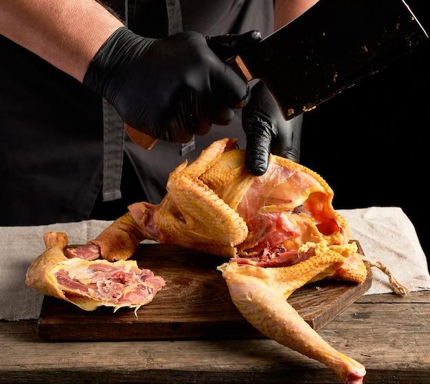 Chef-kok in zwarte uniform en latex handschoenen die rauwe kip in stukken hakken