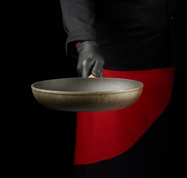 Chef-kok in zwarte uniforme en zwarte latexhandschoenen die lege ronde pan houden