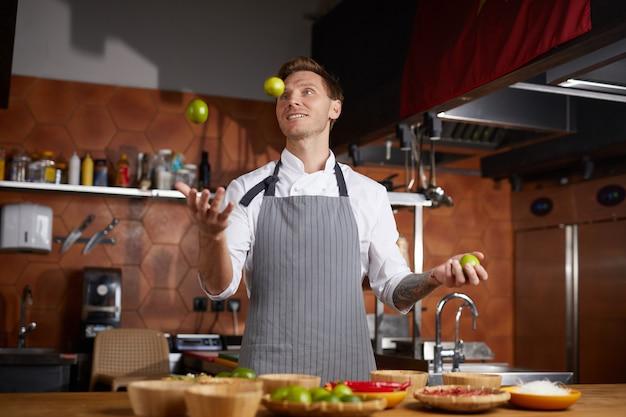 Chef-kok jonglerende vruchten in keuken