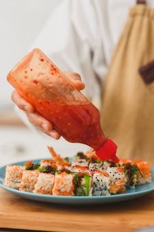 Chef-kok knijp saus op een set sushi-broodjes met roomkaasrijst en zalmsushi-broodjes maken