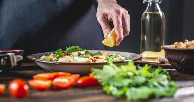 Chef-kok knijpt een citroen uit voor slasaus