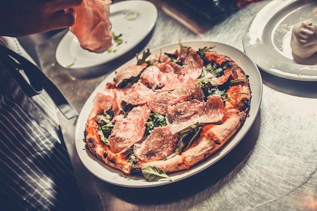 Chef-kok koken een gastronomische smakelijke pizza close-up